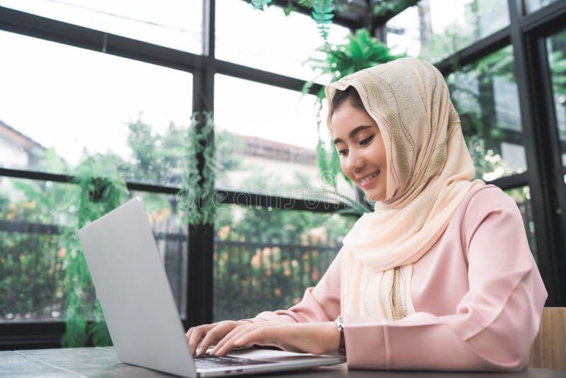 美丽的研究膝上型计算机的年轻人微笑的亚裔回教妇女在家坐在客厅 免版税库存照片