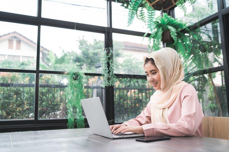 美丽的研究膝上型计算机的年轻人微笑的亚裔回教妇女在家坐在客厅 库存照片