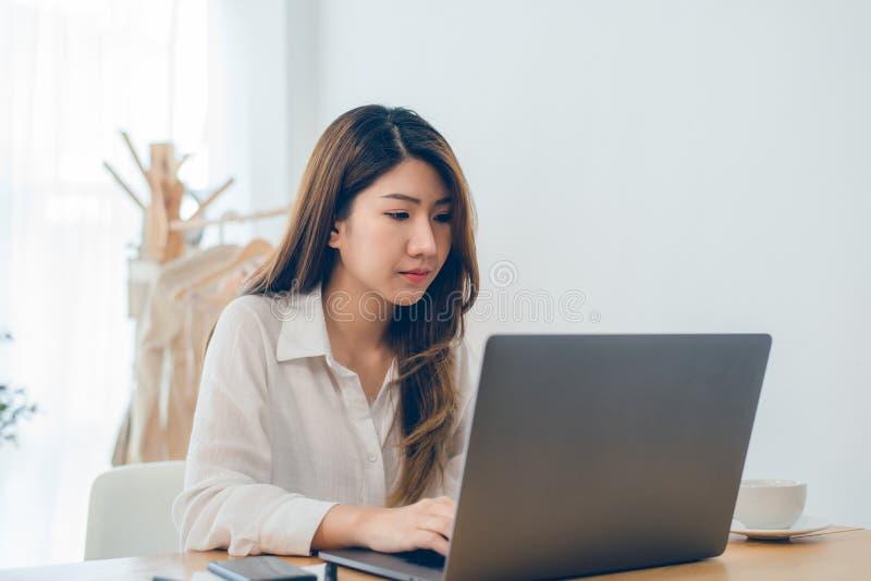 美丽的研究膝上型计算机的年轻人微笑的亚裔妇女,当在家在办公室工作区时 库存照片