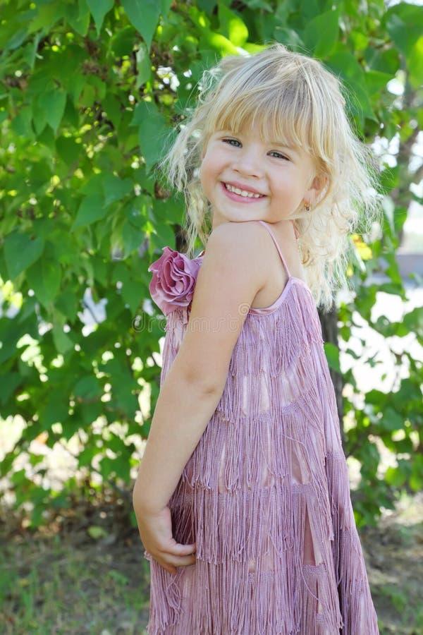 美丽的礼服女孩一点微笑的佩带 免版税库存图片