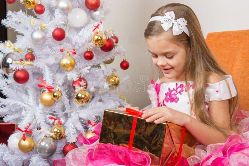 美丽的礼服的七年女孩考虑一件礼物坐长沙发在圣诞树 免版税库存照片