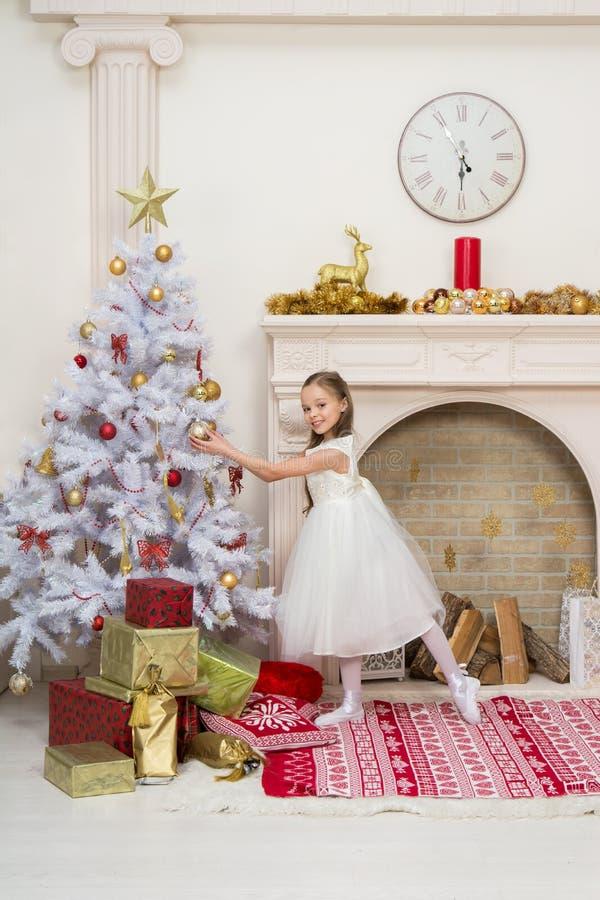 美丽的礼服的小女孩装饰圣诞树 免版税库存图片