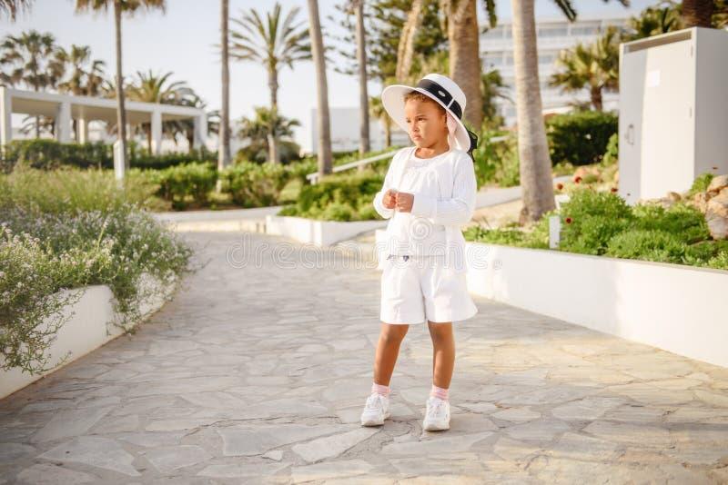 美丽的礼服的,夏天帽子甜矮小的女婴在温暖的晴朗的夏日演奏步行户外 免版税库存照片