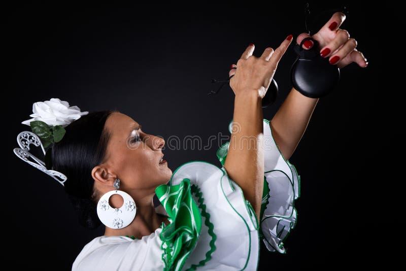 美丽的礼服的年轻佛拉明柯舞曲舞蹈家在黑背景 库存图片