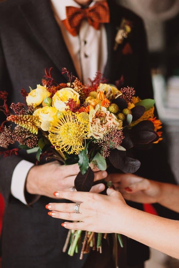 美丽的秋天婚礼花束在一个时髦的新郎的手上一套棕色衣服和橙色蝶形领结的转达在fema的花束 图库摄影