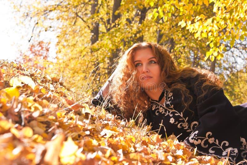 美丽的秋天森林姜头发的妇女 免版税库存照片