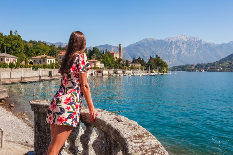美丽的科莫湖的在Tremezzina,伦巴第,意大利妇女旅客 有传统房子和清楚的蓝色的风景小镇 库存图片
