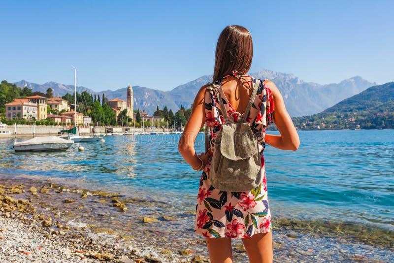 美丽的科莫湖的在Tremezzina,伦巴第,意大利妇女旅客 有传统房子和清楚的蓝色的风景小镇 免版税库存图片