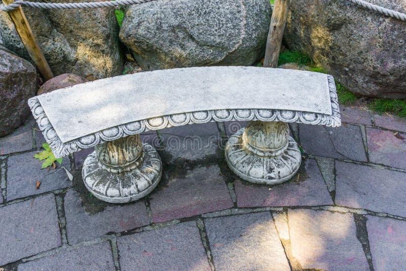 美丽的空的石头希腊时髦的长凳在庭院里 库存照片