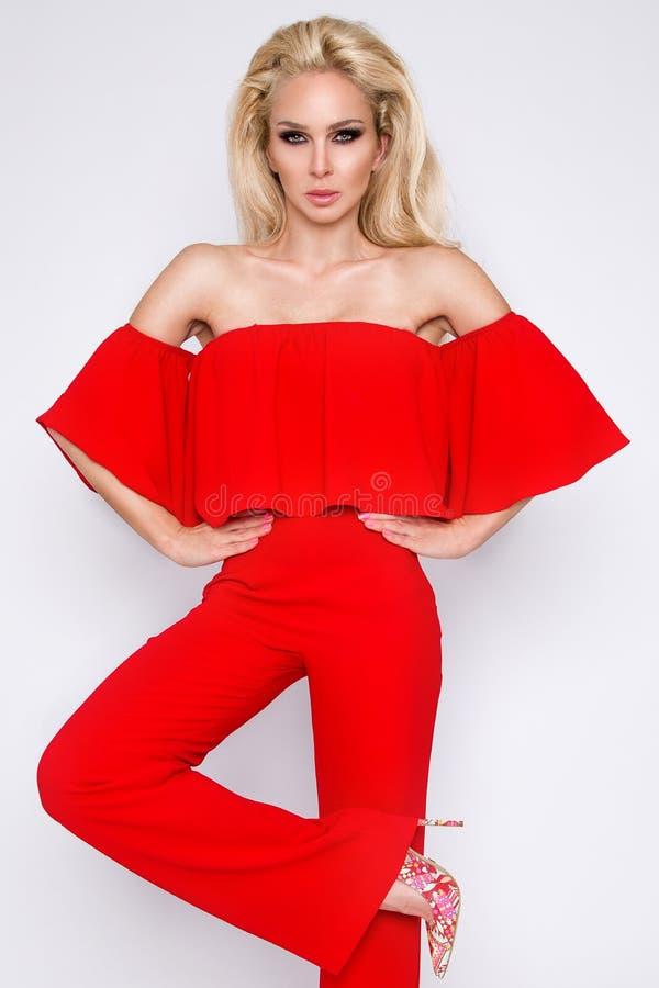 美丽的站立在白色背景的妇女性感的时装模特儿穿着有装饰衣裙的红色衣服 库存照片