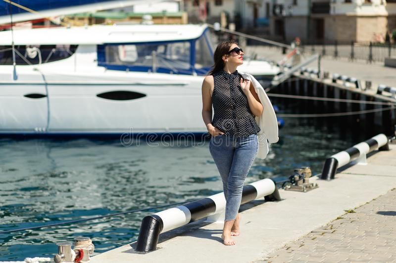 美丽的笑的妇女时髦白色成套装备摆在白色游艇背景的太阳镜的 免版税图库摄影