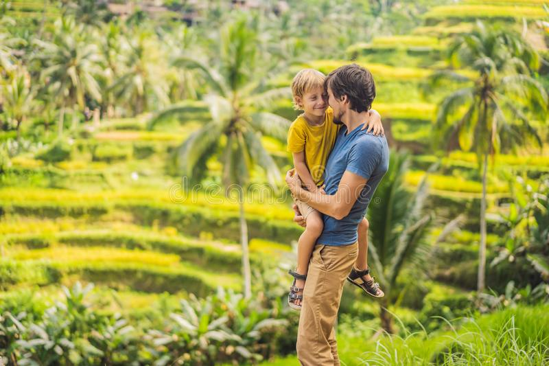 美丽的米大阳台的爸爸和儿子旅客以著名火山为背景在巴厘岛,印度尼西亚旅行 免版税库存照片