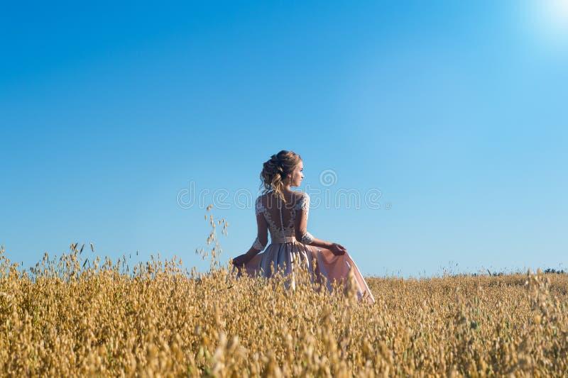 美丽的米黄礼服的迷人的女孩在领域黑麦 免版税图库摄影