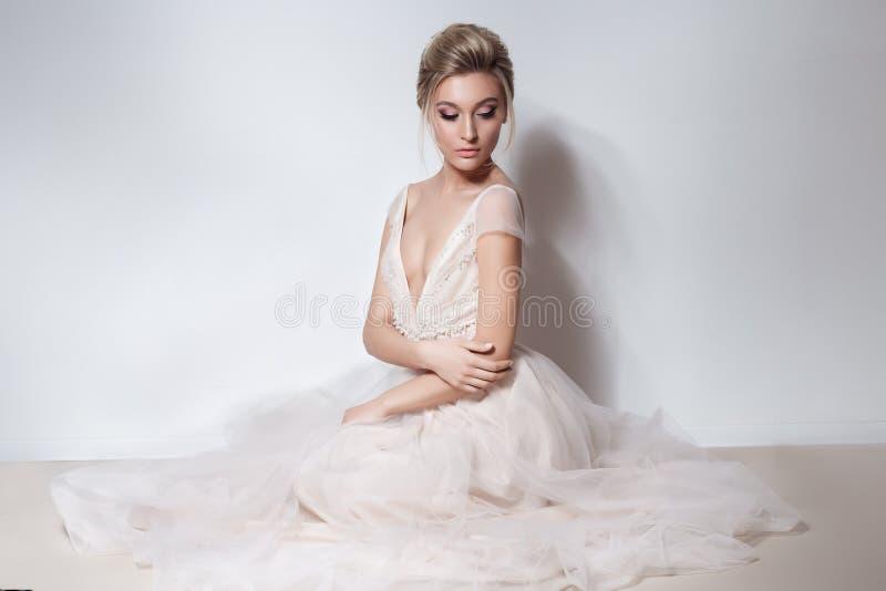 美丽的精美软的桃红色skazachno婚礼礼服的新娘性感的女孩与在胸口和后面的裁减与构成和晚上h 图库摄影