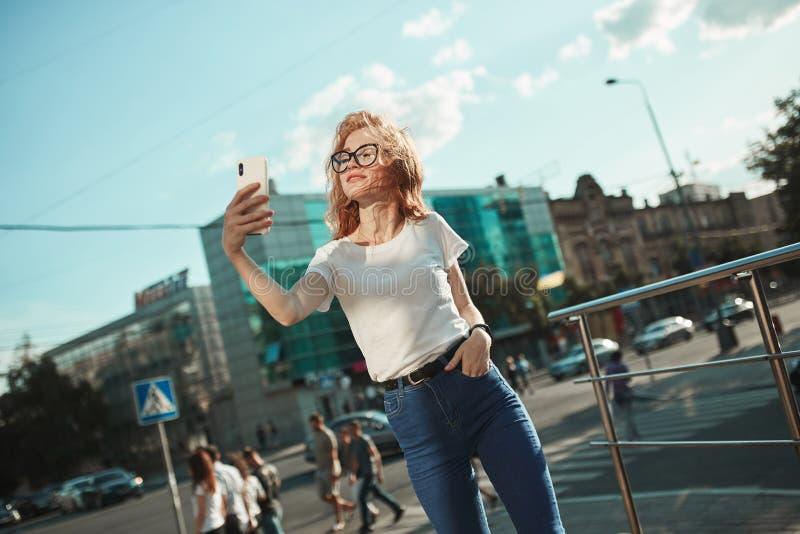 美丽的红发女孩在城市的背景的街道站立并且采取在她的手机的一selfie 女孩是 库存照片