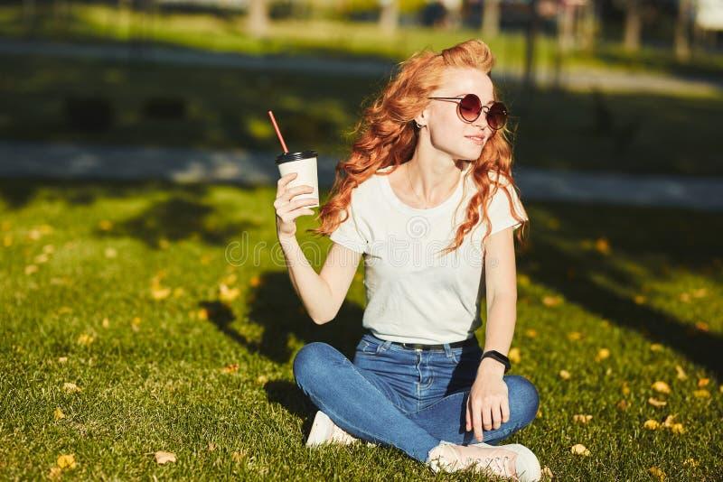 美丽的红发女孩坐草坪 在女孩的手上一杯咖啡 少女温暖早晨 免版税库存照片
