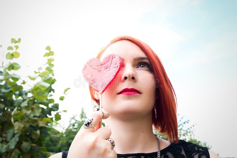 美丽的红发女孩用在shap的糖果盖她的眼睛 免版税库存照片