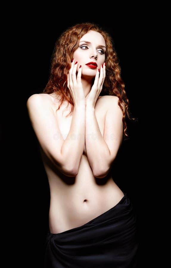美丽的红发妇女演播室画象黑背景的 库存照片