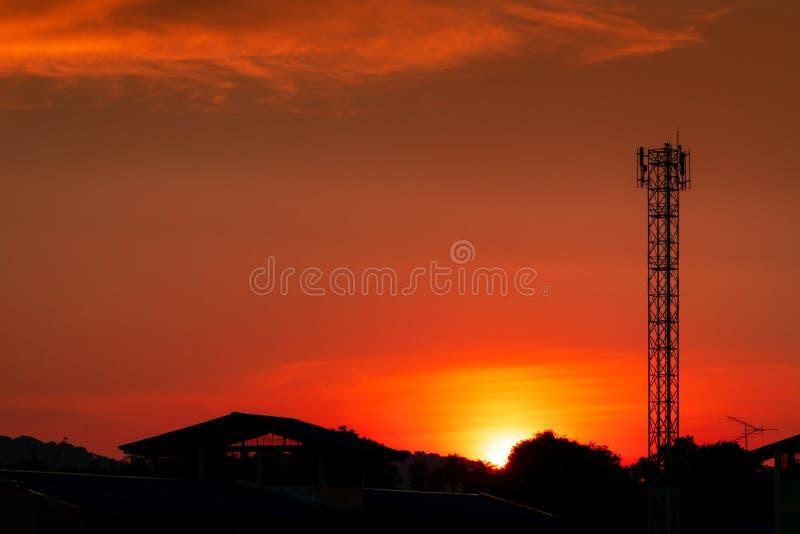 美丽的红色和橙色日落天空 剪影电信塔和树在与美丽的红色日落天空的晚上 免版税库存照片