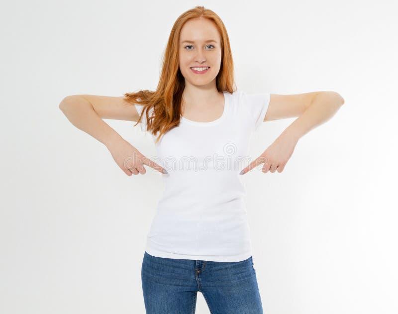 美丽的红色头发女孩在被隔绝的白色T恤指向了 俏丽的T恤杉嘲笑的微笑红色顶头妇女,空白 库存照片