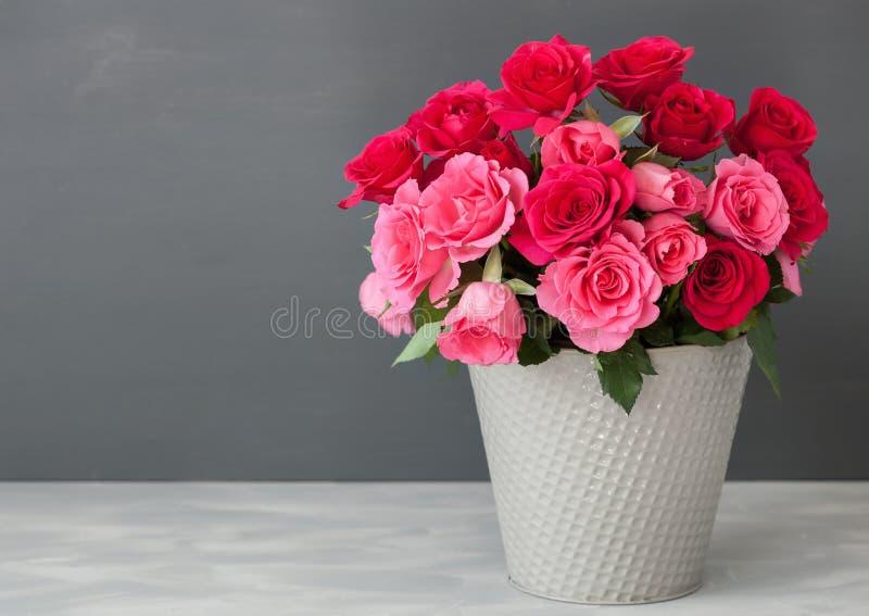 美丽的红色玫瑰开花在花瓶的花束在灰色 免版税库存图片