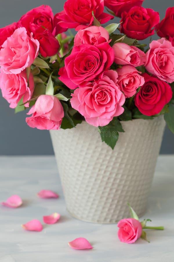 美丽的红色玫瑰开花在花瓶的花束在灰色 库存图片