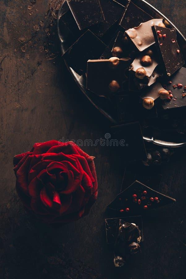 美丽的红色玫瑰花和被分类的可口巧克力片顶视图  免版税库存照片
