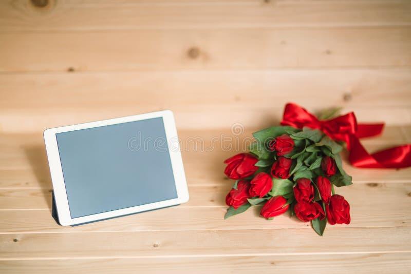 美丽的红色郁金香和片剂在木背景 库存照片