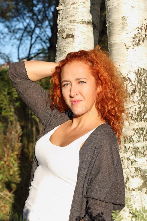 美丽的红色头发妇女在白桦树附近站立 免版税库存图片