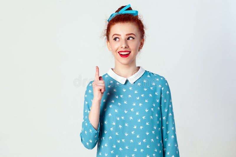 美丽的红头发人女孩有想法,并且她举她的手指  库存图片