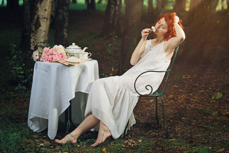 美丽的红头发人妇女在超现实的森林里 库存图片