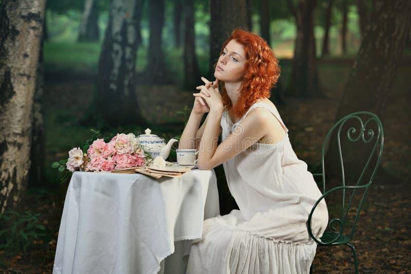 美丽的红头发人妇女食用茶在森林 免版税库存图片