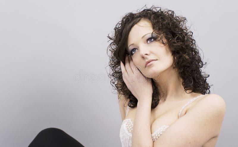 美丽的纵向坐的妇女年轻人 免版税库存照片