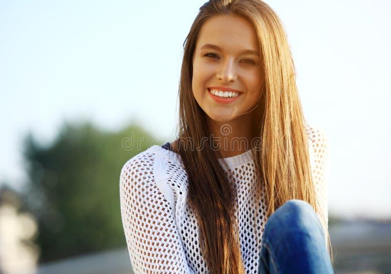 美丽的纵向微笑的妇女年轻人 一新和美好年轻时装模特儿摆在的特写镜头画象室外 免版税库存照片