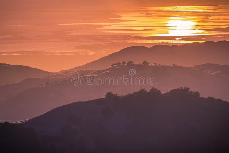 美丽的绵延山在日落光沐浴了;落日在旧金山湾的水中反射了的 库存图片