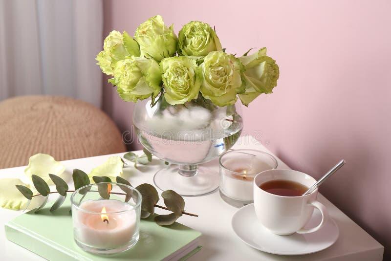 美丽的绿蔷薇、蜡烛和茶花束在桌上的 免版税库存图片