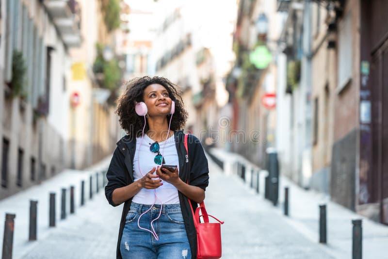美丽的美国黑人的在耳机的女孩听的音乐户外 免版税库存照片