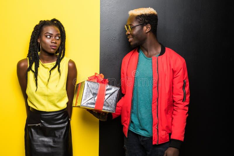 美丽的美国黑人的女孩和英俊的人拿着一个礼物,看彼此并且微笑着,隔绝在颜色backgrou 免版税库存图片