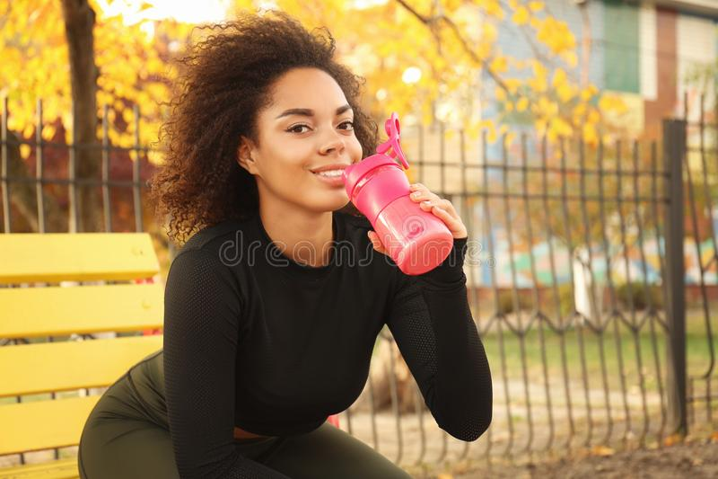 美丽的美国黑人的妇女饮用的蛋白质震动, 库存照片