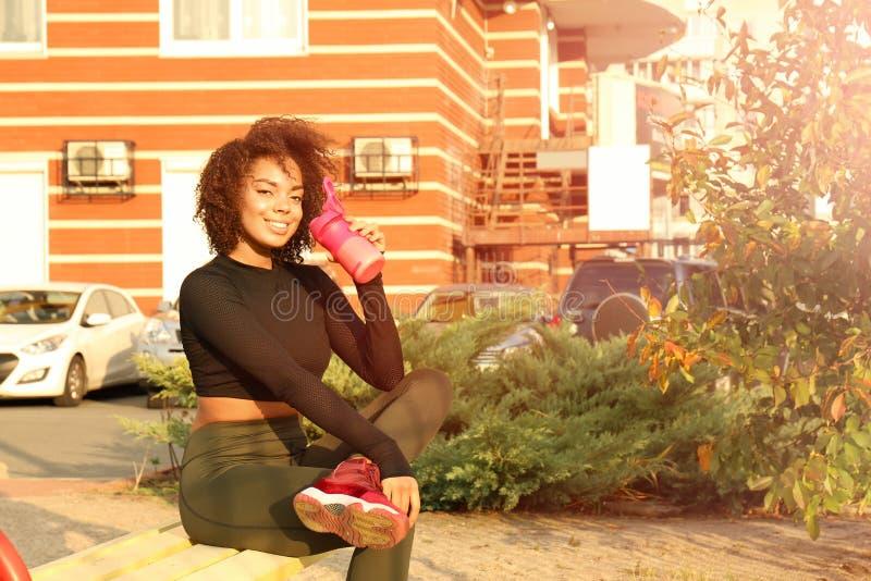 美丽的美国黑人的妇女饮用的蛋白质震动 库存图片