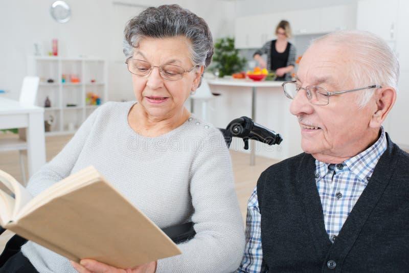 美丽的老夫妇阅读书和微笑 免版税库存图片