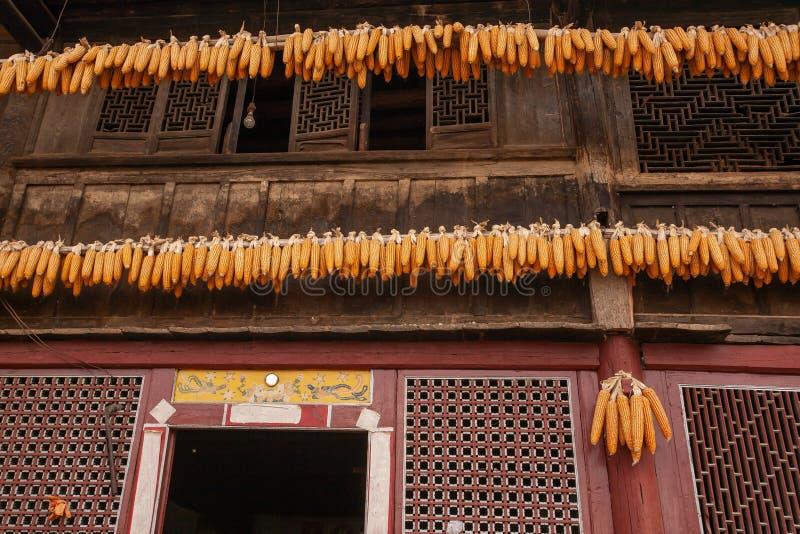 美丽的老迷人的中国房子,美好的艺术木纹理,垂悬在门的玉米干燥 城子村, 免版税库存图片