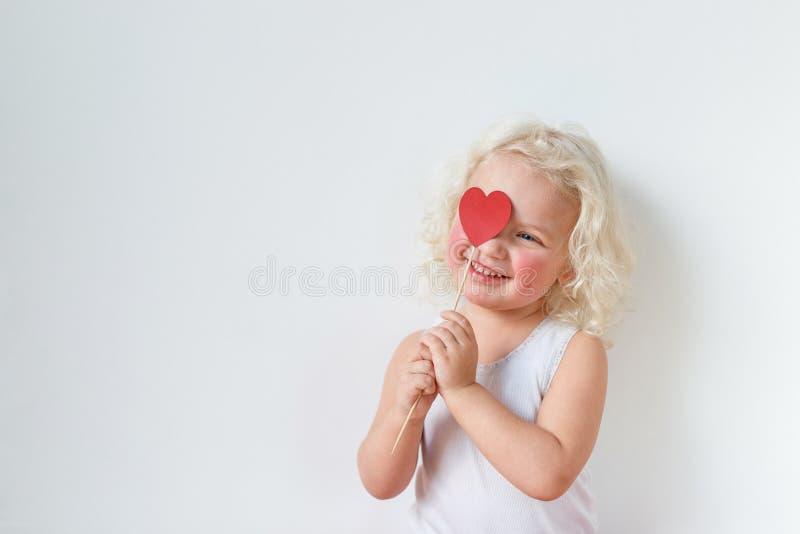 美丽的胭脂微笑的愉快的女孩用心脏棍子盖面孔,有宜人的微笑,被隔绝在白色 免版税库存照片