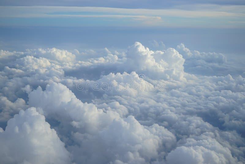 美丽的自由格式密集的白色云彩看法与蓝天背景树荫的从飞行飞机窗口的 库存照片