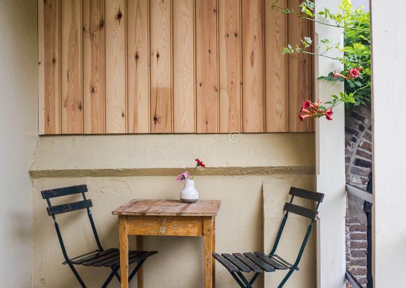美丽的舒适大阳台或阳台有小桌、椅子和花的 被定调子的图象 免版税库存照片