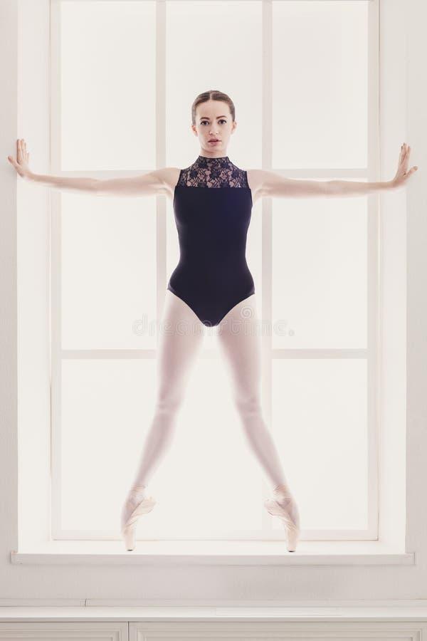 美丽的芭蕾舞女演员在releve芭蕾位置站立 免版税库存照片