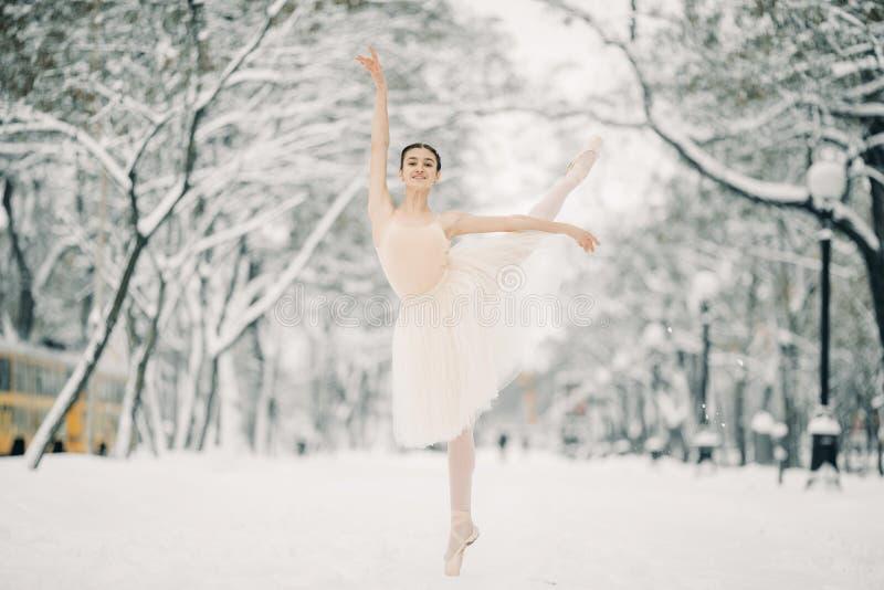 美丽的芭蕾舞女演员跳舞在多雪的城市走道  免版税图库摄影