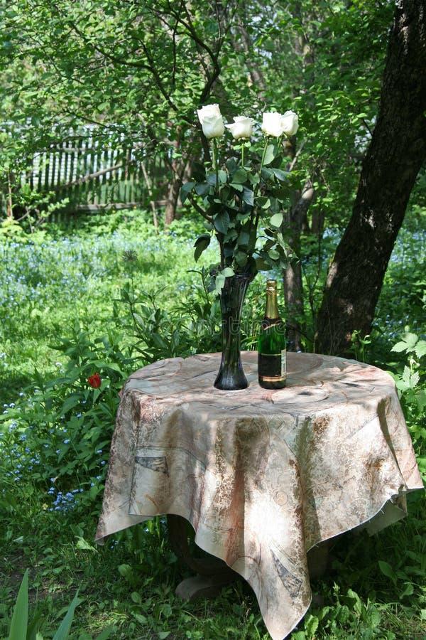美丽的花和一个瓶好酒为假日 免版税图库摄影