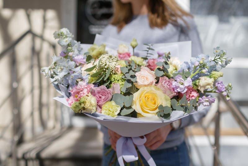 美丽的花花束在妇女` s手上 Floristry概念 背景上色新绿色洗衣店春天空白黄色 卖花人的工作花的 库存照片