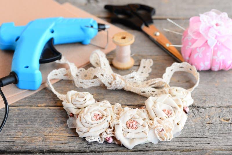 美丽的花织品项链,胶合热的枪,剪刀,螺纹,针,在葡萄酒木桌上的毛毡 创造项链 免版税库存图片